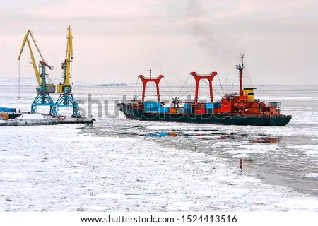 A cargo ship with containers near the pier of the seaport. Maritime navigation and shipping in the Arctic. The ship passes among the ice floes. Anadyr Sea Port, Chukotka, Far East Russia. November. #1524413516