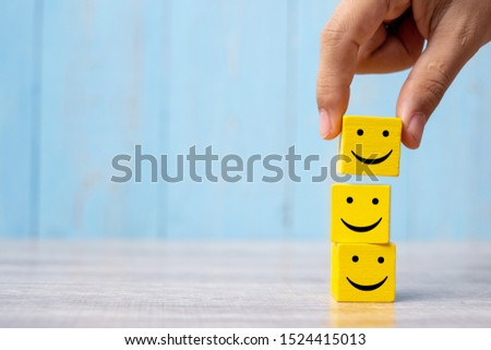 smile face on yellow wood cube. Service rating, ranking, customer review, satisfaction and emotion concept. #1524415013