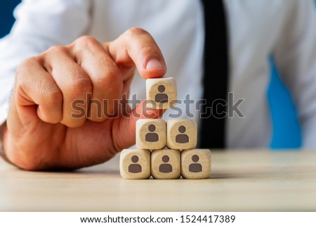 Business executive stacking wooden dices  with people icons on them in a pyramid shape in a conceptual image. #1524417389