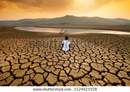 Climate change and global warming concept. Children sitting on drying lake with the sky turning orange by an pollution from industrial or city. #1524421928