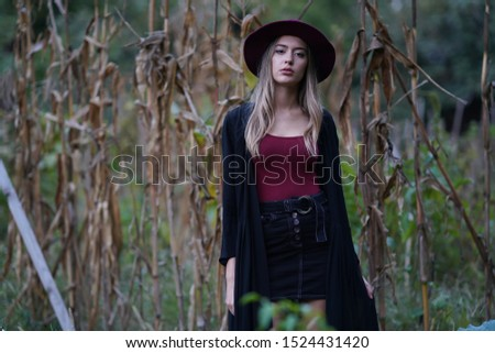 portrait of girl in red blouse, black cardigan and red hat in the vegetable garden #1524431420