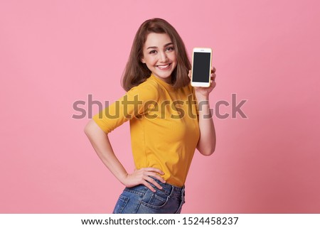 Portrait of happy young woman showing at blank screen mobile phone isolated over pink background. #1524458237