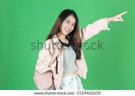 Attractive young Asian tourist girl with bag ready to travel over green isolated background. #1524462650