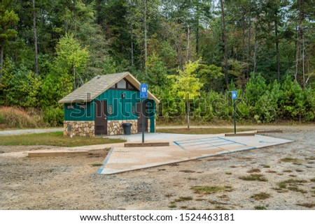 Brand new restrooms in a park with handicap parking in the woodlands on a bright sunny afternoon in early autumn #1524463181