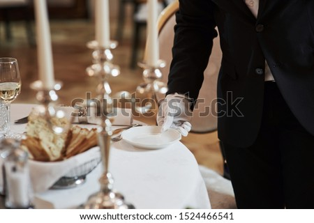 Holds white plate. Process of preparing place for special visitors. Waiter in classical wear works on the servering. #1524466541