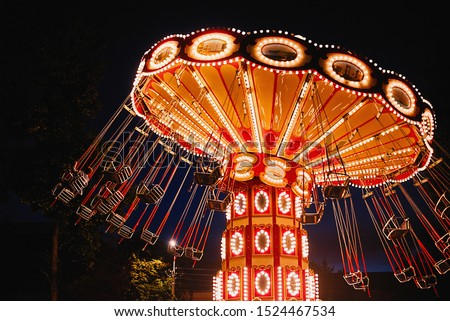Illuminated swing chain carousel in amusement park at night Royalty-Free Stock Photo #1524467534