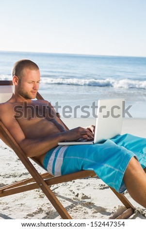 Handsome man on the beach using his laptop sitting on his deck chair #152447354