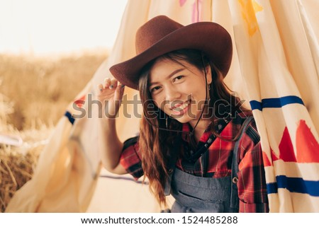 Cowgirl woman smiling happy on american prairie wearing cowboy hat. Asian Caucasian girl in countryside