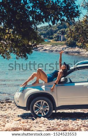 woman sitting on car hood looking on the sea beach seaside