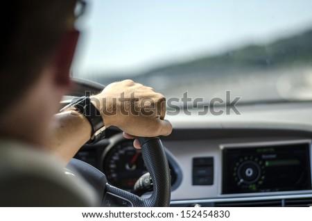 Generic photo of man driving a car through slight turn. Royalty-Free Stock Photo #152454830