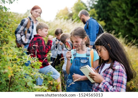 Group of school children with teacher on field trip in nature, learning science. #1524565013