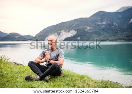 A senior man pensioner sitting by lake in nature, doing yoga exercise. #1524565784
