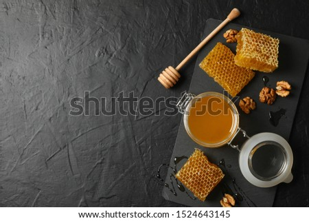 Walnut, honeycombs, jar with honey and dipper on black background, copy space #1524643145