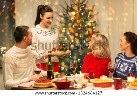 holidays and celebration concept - happy friends having christmas dinner at home #1524664127