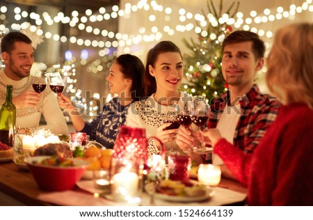 winter holidays and people concept - happy friends celebrating christmas at home feast and drinking red wine #1524664139