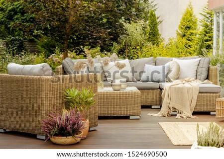 Wicker furniture on a wooden terrace of modern house