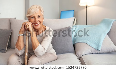 Smiling grandmother sitting on couch. Portrait of a beautiful smiling senior woman with walking cane on light background at home. Old woman sitting with her hands on a cane #1524728990
