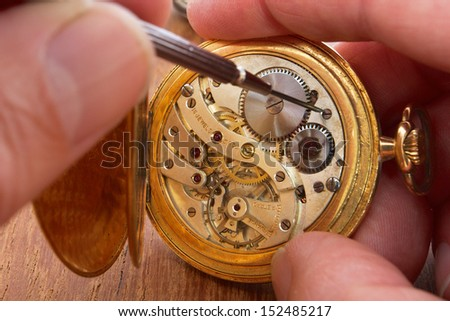 hands that repair an old pocket watch #152485217