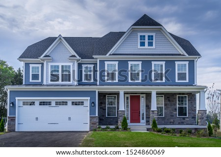 Luxury American colonial traditional home w/ two car garage, covered porch, pacific blue horizontal vinyl and sterling gray shingle siding, fiber cement shingle gable roof, window trim, stone cladding #1524860069