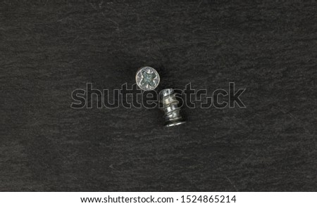 Group of two whole glossy metallic glossy bolt flatlay on grey stone #1524865214