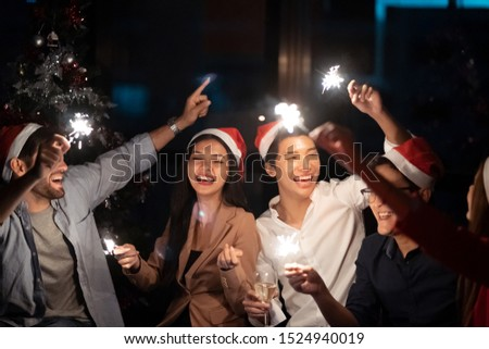 Group of diversity people having great Christmas party in working office together at night. They celebrate with champagne and holding sparklers feeling happy and enjoy laughing. Xmas, new year concept #1524940019
