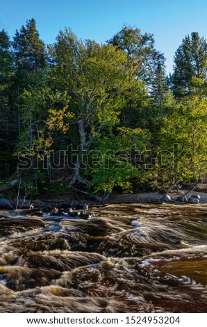 The Hurricane River pours out of the forest and rushes into Lake Superior at it's mouth, Pictured Rocks National Lakeshore, Alger County, Michigan