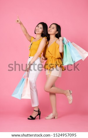 Asian pretty young woman sitting on pink  pastel background. She smiling and  happy shopping bags. she nice-looking lovely attractive shine.Friend happy to shopping time. #1524957095
