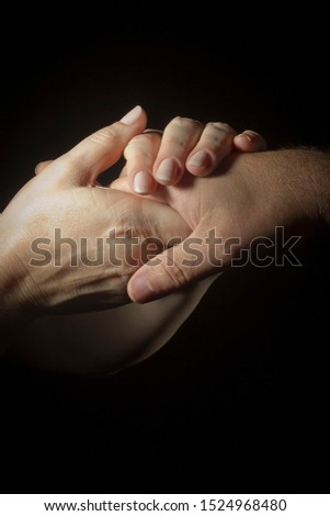 Female hands hold a man's hand on a black background #1524968480
