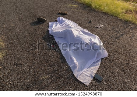 Concept of crime murder scene, High angle view of chalk outlined death body with bllody knife under white cloth on road. Royalty-Free Stock Photo #1524998870