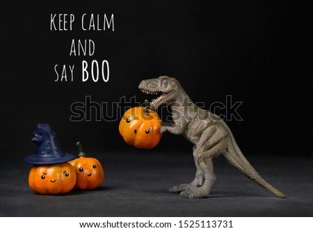 keep calm and say BOO. halloween card. Dinosaur and halloween pumpkins on black background. Tyrannosaurus Rex holding orange pumpkin.