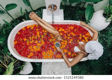 Woman with wrapped towel on head is drinking tea or coffee while relaxing in outdoor bath with flowers in Bali spa hotel, top view from above. #1525149380