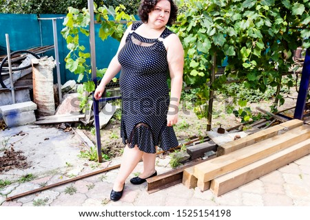 pictured in the photo owerweight woman in a black sundress white polka dots #1525154198