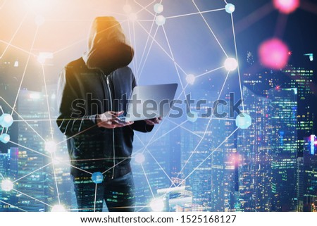 Unrecognizable young hacker with laptop standing in night city with double exposure of glowing network interface. Concept of cybercrime. Toned image #1525168127