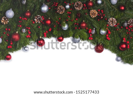 Christmas Border frame of tree branches on white background with copy space isolated, red and silver decor, berries, stars #1525177433