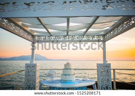 Wedding cake photographed at sunset over the sea #1525208171