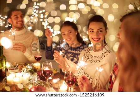 winter holidays and people concept - happy friends with sparklers celebrating christmas at home feast #1525216109