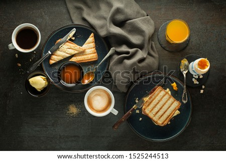 Breakfast served with coffee, juice, toast sandwich, boiled egg, and jam with butter. Delicious healthy breakfast. #1525244513