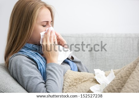 Portrait of a young woman sneezing in to tissue Royalty-Free Stock Photo #152527238