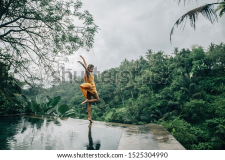 Happy woman enjoying warm tropical rain falling on her on infinity pool with a jungle view in Ubud, Bali #1525304990
