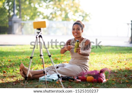 Lifestyle blogger. Lifestyle blogger sitting on grass and making video about healthy diet #1525310237