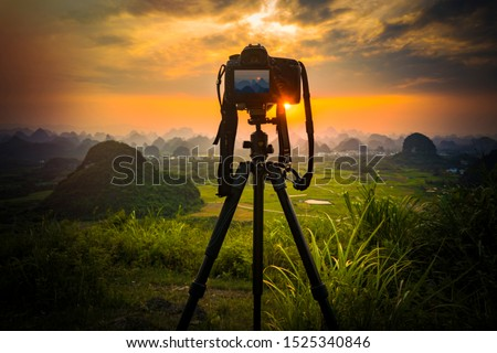 Camera on tripod and photography view camera with blurred focus landscape of sunset sunrise sun light sky cloud