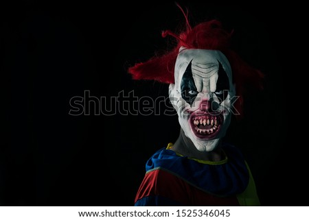 closeup of a scary evil clown with red hair, white eyes, bloody teeth and a threatening look staring at the observer, against a black background with some blank space #1525346045