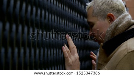 sorrowful man is touching by forehead metal grid outside in city yard in daytime #1525347386