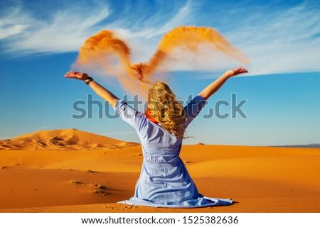 Girl plays with sand in the Sahara desert. Erg Chebbi, Merzouga,  Morocco. Motion blur. Royalty-Free Stock Photo #1525382636