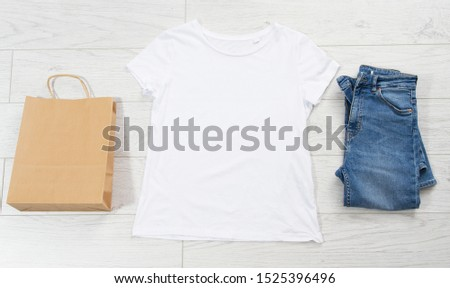 White t-shirt, blue denim and empty paper bag copy space top view, overhead view of woman's casual  #1525396496