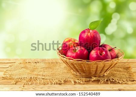 Apples in basket on wooden table over garden bokeh background