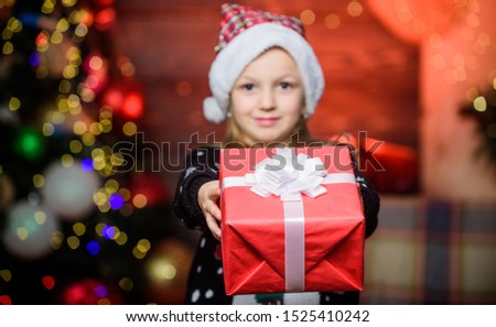Nothing warms the heart like giving xmas gift. Happy little girl giving xmas present. Small child holding present on xmas day. Adorable kid with beautifully wrapped xmas gift. #1525410242