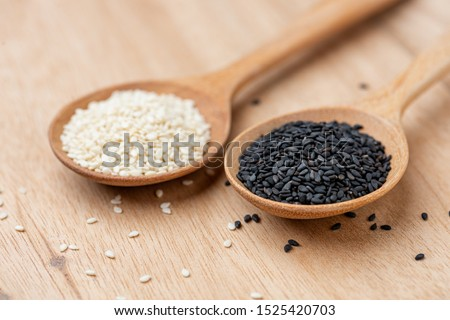 close up of black sesame and white sesame seed on wooden spoon in kitchen. #1525420703