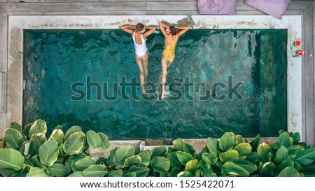 Family mom and teen child relaxing at pool on Bali private villa, top view from above #1525422071