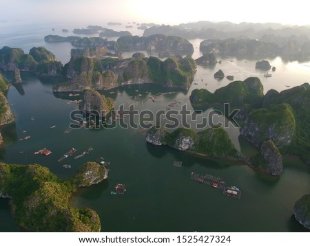 Aerial view floating fishing village and rock island, Halong Bay, Vietnam, Southeast Asia. UNESCO World Heritage Site. Famous destination of Vietnam Royalty-Free Stock Photo #1525427324